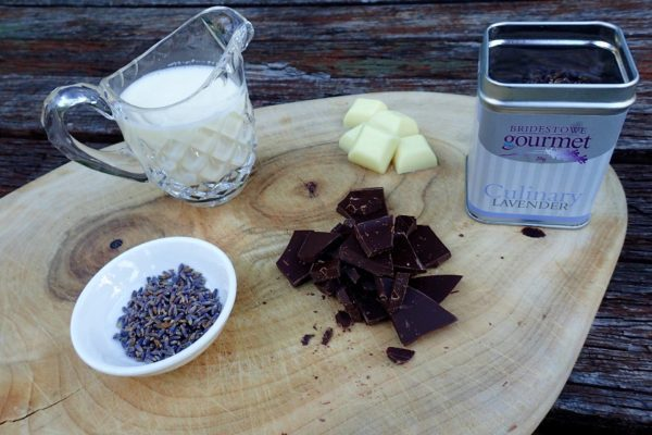 Chocolate, lavender and jug of milk prepared on a chopping board.