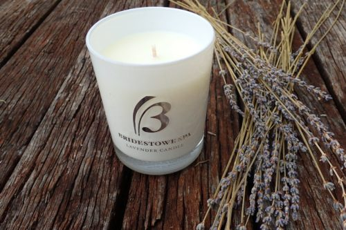 Lavender candle on wooden table with bunch of lavender.