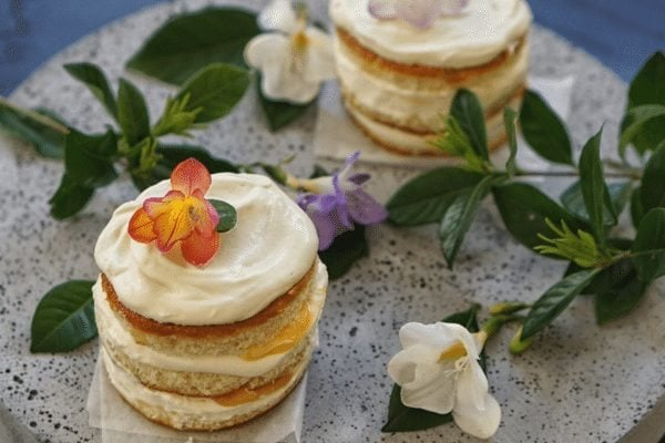 Two gin sponge cakes with lavender cream decorated with flowers.